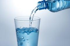 Hällande vatten från flaskan in i exponeringsglas arkivfoto