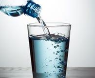 Hällande vatten från flaskan in i exponeringsglas royaltyfria foton