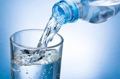 Hällande vatten från flaskan in i exponeringsglas på blå bakgrund Royaltyfri Bild