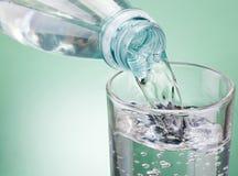 Hällande vatten från flaskan in i exponeringsglas på grön bakgrund royaltyfria bilder