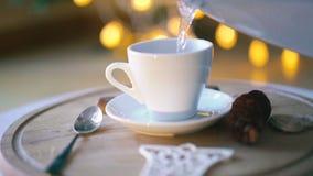 Hällande vatten in i en kopp kaffe i 4K lager videofilmer