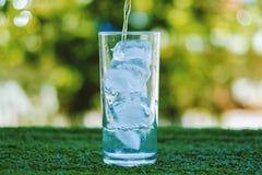 Hällande vatten in i ett exponeringsglas av is arkivbild