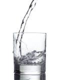 Hällande vatten in i ett exponeringsglas på vit bakgrund royaltyfri bild