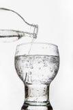 Hällande vatten in i ett exponeringsglas på vit bakgrund Arkivbild