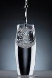 Hällande vatten in i ett krökt skottexponeringsglas Arkivbild