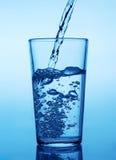 Hällande vatten in i exponeringsglas Arkivbild