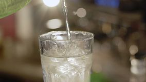 Hällande vatten in i exponeringsglas för lemonad långsamt stock video