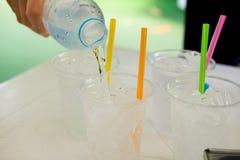 Hällande vatten i genomskinliga plast-koppar med sugrör Arkivbild