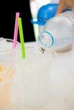 Hällande vatten i genomskinliga plast-koppar med sugrör Royaltyfria Foton