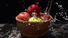 Hällande vatten på de röda och gröna äpplena i en bambukorg på svart bakgrund lager videofilmer