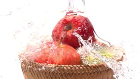 Hällande vatten på de röda och gröna äpplena i en bambukorg på vit bakgrund stock video