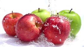 Hällande vatten på de röda och gröna äpplena på vit bakgrund arkivfilmer