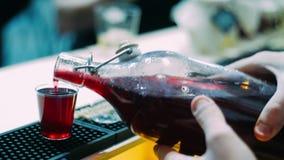 Hällande vin för bartender från flaskan in i exponeringsglas på räknare f?rbereda sig f?r deltagare arkivfilmer