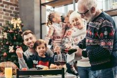 hällande vin för lycklig farfar in i exponeringsglas för hans familj arkivfoton