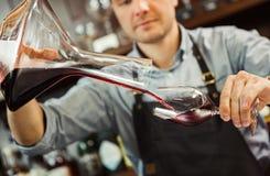 Hällande vin för Sommelier in i exponeringsglas från plastbunken male uppassare Arkivfoto