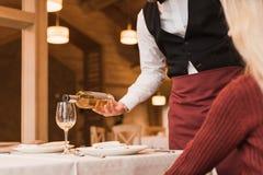Hällande vin för uppassare in i exponeringsglas Arkivfoton