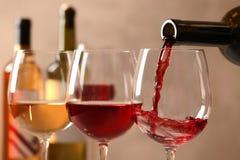 Hällande vin från flaskan in i exponeringsglas på suddig bakgrund royaltyfria bilder
