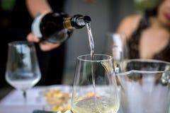 Hällande vin in i exponeringsglaset Arkivfoton