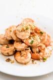 Hällande vitlök på Fried Shrimp, vit maträtt, vit bakgrund, Wh Arkivbild