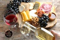 Hällande vitt vin för kvinna in i exponeringsglas på tabellen med läcker mat royaltyfri foto