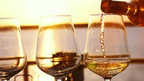 Hällande vitt vin i exponeringsglas på den fantastiska solnedgången med havssikt i strandrestaurang royaltyfri fotografi