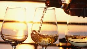 Hällande vitt vin i exponeringsglas på den fantastiska solnedgången vid havet i tropiskt strandkafé fotografering för bildbyråer