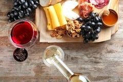 Hällande vitt vin in i exponeringsglas på tabellen med läcker mat arkivfoton