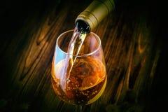 Hällande vitt vin in i exponeringsglaset mot träbakgrund Arkivfoto