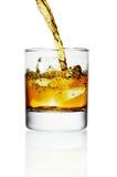 hällande whiskey för glass is arkivbilder