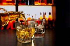 Hällande whisky för bartender framme av whiskyexponeringsglas och flaskor Royaltyfri Bild