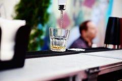 Hällande whisky för bartender in i ett exponeringsglas fotografering för bildbyråer