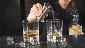 Hällande whisky för kvinnlig bartender ut ur grej i ultrarapid Oigenkännlig kvinnlig bartender i svart likformig HD arkivfilmer