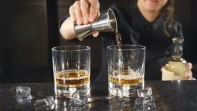 Hällande whisky för kvinnlig bartender ut ur grej i ultrarapid Oigenkännlig kvinnlig bartender i svart skjorta HD stock video