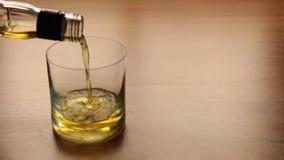H?llande whisky fr?n flaskan in i exponeringsglas p? tabellen stock video