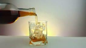 Hällande whisky med flaskan i det dricka exponeringsglaset med iskuber på varm guld- bakgrund, tid av kopplar av drinken med whis arkivfilmer