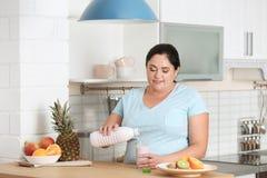 Hällande yoghurt för kvinna från flaskan in i exponeringsglas i kök arkivfoton