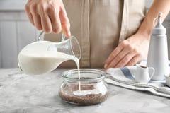 Hällande yoghurt för kvinna in i den glass kruset med chiafrö royaltyfri bild