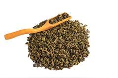 Hällde grönt teguaninte för kines, spritt på en vit bakgrund, med en tespatel och ett tefilter royaltyfri fotografi