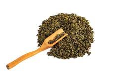 Hällde grönt teguaninte för kines, spritt på en vit bakgrund, med en tespatel och ett tefilter royaltyfria foton