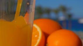 Hällde orange fruktsaft för närbilden in i ett exponeringsglas lager videofilmer