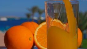 Hällde orange fruktsaft för närbilden in i ett exponeringsglas stock video