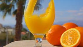 Hällde orange fruktsaft för närbilden in i ettexponeringsglas stock video