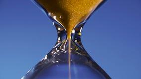 Hälls guld- sand för timglaset i en genomskinlig flaska på en blå bakgrund som interpunkterar kortvarigheten av tid lager videofilmer