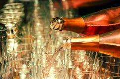 Hällt rött vin in i exponeringsglas Arkivbilder