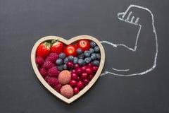 Hälsa bantar abstrakt begrepp för hjärta med strongmanhanden på svart tavla royaltyfri bild