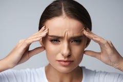 hälsa Den härliga kvinnan som har den starka huvudvärken som känner sig smärtar Royaltyfri Bild