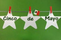 Hälsa för Cinco de Mayo meddelande som är skriftligt över vita hängande pinnor för stjärnor och för Mexico flagga på en linje Arkivfoton