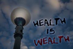 Hälsa för ordhandstiltext är rikedom Affärsidéen för att vara i det sunda staget för stort värde för bra form äter sunda ljusa st Royaltyfri Bild