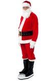 Hälsa medvetna Santa som kontrollerar hans vikt Fotografering för Bildbyråer
