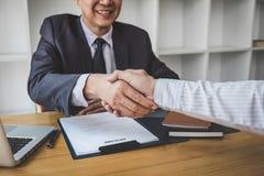 Hälsa nya kollegor, handskakningen medan jobb som intervjuar, den manliga kandidaten som skakar händer med intervjuaren eller arb royaltyfri foto